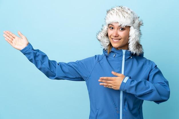 Молодая уругвайская девушка в зимней шапке на синей стене протягивает руки в сторону для приглашения прийти