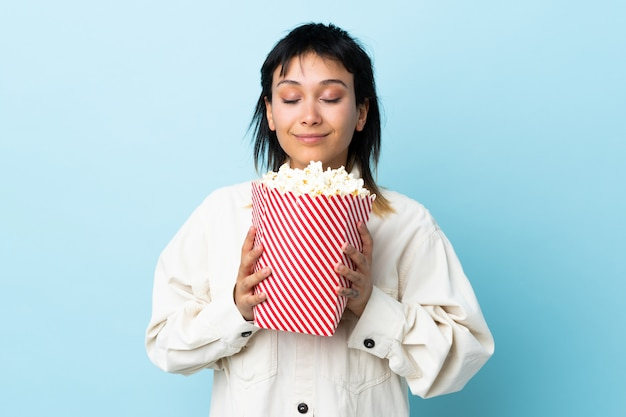 Молодая уругвайская женщина над синей стеной держит большое ведро попкорна