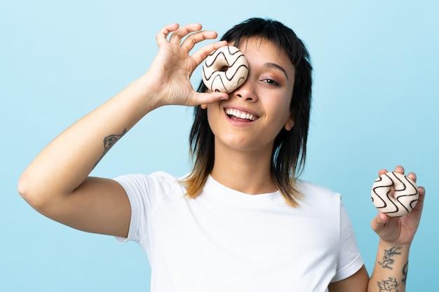 Молодая уругвайская женщина над синей стеной держит пончик и счастлива
