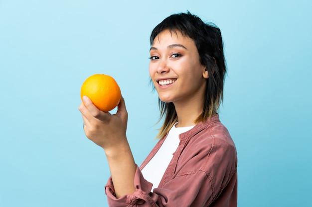 Молодая уругвайская женщина над синей стеной держит апельсин
