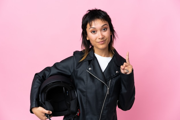 Молодая уругвайская женщина, держащая мотоциклетный шлем над розовой стеной, указывая указательным пальцем на отличную идею