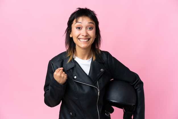 Молодая уругвайская женщина, держащая мотоциклетный шлем над розовой стеной, празднует победу