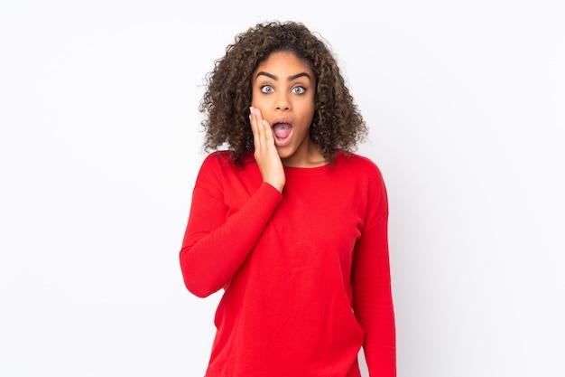 Молодая афро-американская женщина на стене с удивлением и шокирован выражением лица
