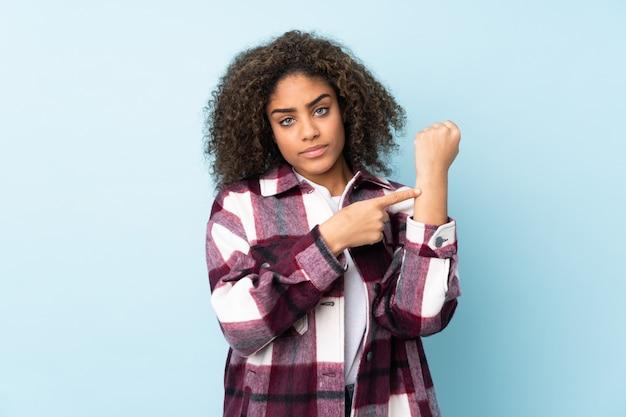 Молодая афро-американская женщина на голубой стене делая жест опоздания