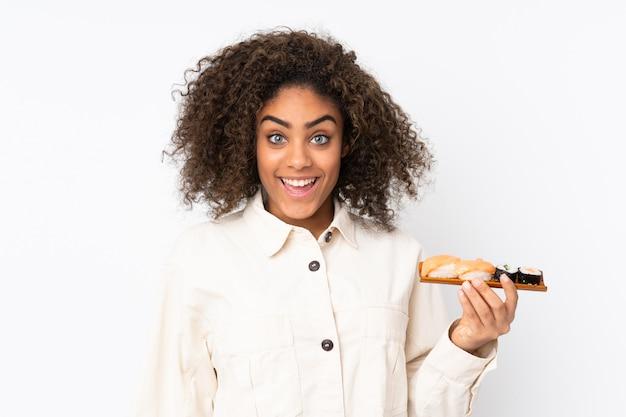 Молодая афроамериканец женщина, держащая суши на белой стене с удивлением и шокирован выражением лица