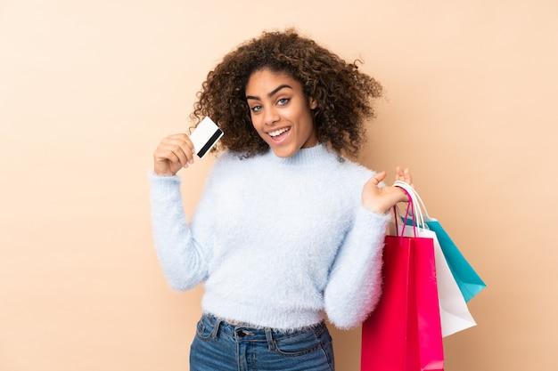 Молодая афро-американская женщина на бежевой стене держа хозяйственные сумки и кредитную карточку