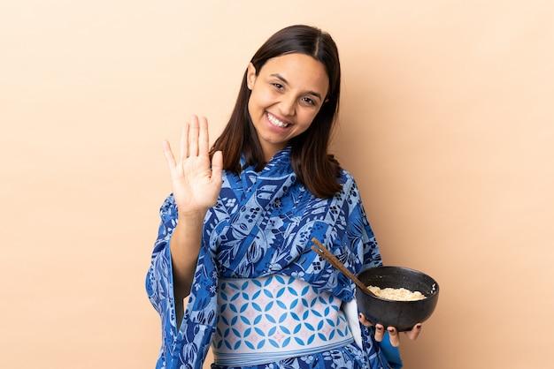 Женщина носит кимоно и держит миску с лапшой, салютовавшей рукой со счастливым выражением, держа миску лапши с палочками для еды