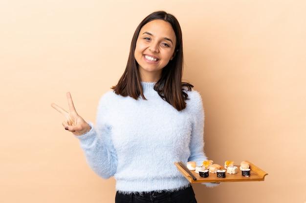 壁に寿司を両手で勝利のサインを示す若いブルネット混血女性