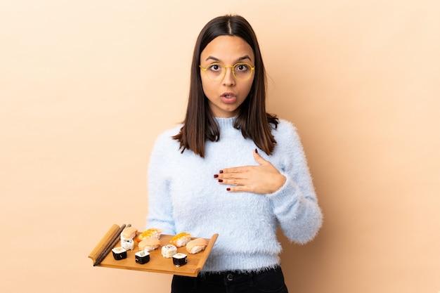 壁を見下ろす寿司を保持している若いブルネットの混血女性驚いて、右を見ながらショックを受けた