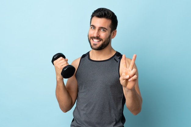 笑みを浮かべて、勝利のサインを示す重量挙げを作るひげを持つ若いスポーツ男