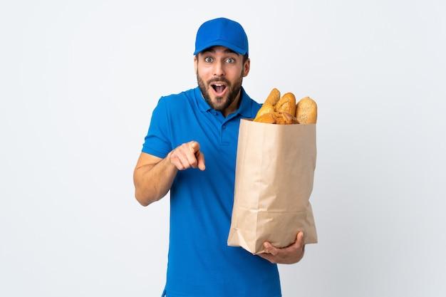 Доставка человек, держащий мешок с хлебом на белой стене удивлен и указывая вперед
