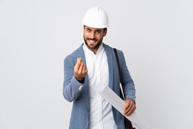 Молодой архитектор человек с шлемом и проведение чертежи на белой стене, делая деньги жест
