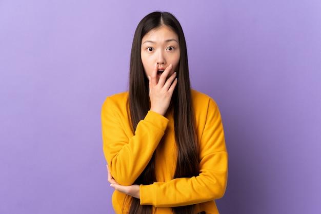 紫の壁を越えて若い中国人の女の子は右を見ながら驚いてショックを受けた