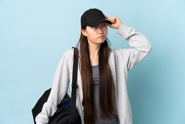 頭に指を置く狂気のジェスチャーを作る青い壁にスポーツバッグを持つ若いスポーツ中国の女性