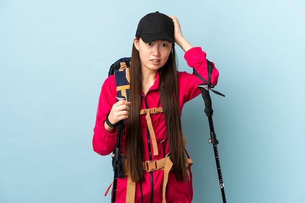 緊張のジェスチャーをしている青い壁の上のバックパックとトレッキングポールを持つ若い中国人の女の子