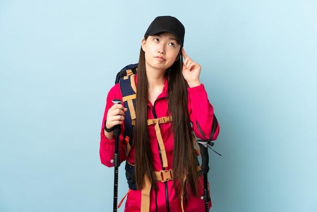 バックパックと青い壁を越えてトレッキングポールを持つ中国の少女、頭に指を置く狂気のジェスチャー