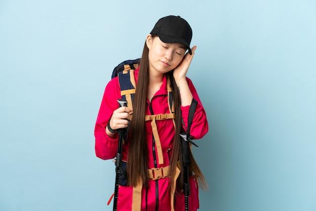 バックパックとトレッキングポールを持つ中国の少女、青い壁を越えて愛らしい表現で睡眠ジェスチャーを作る