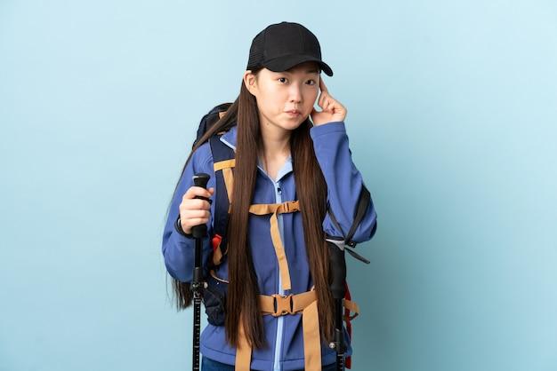 アイデアを考えて青い壁にバックパックとトレッキングポールを持つ中国の少女