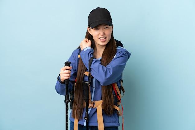 勝利を祝う青い壁の上のバックパックとトレッキングポールを持つ若い中国人の女の子