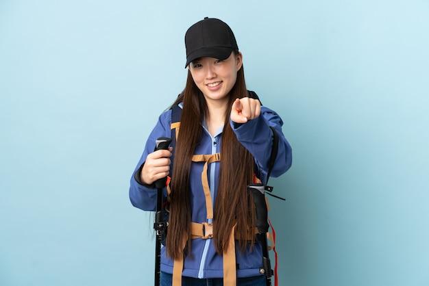 幸せな表情でフロントを指している青い壁にバックパックとトレッキングポールを持つ中国の少女