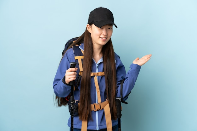 バックパックと青い壁の上のトレッキングポールを持つ中国の少女に向かって笑顔を見ながらアイデアを提示