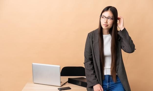 Китайская деловая женщина на своем рабочем месте, имея сомнения