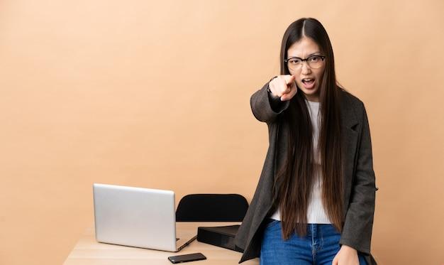 Китайская деловая женщина на ее рабочем месте разочарованы и указывая на фронт
