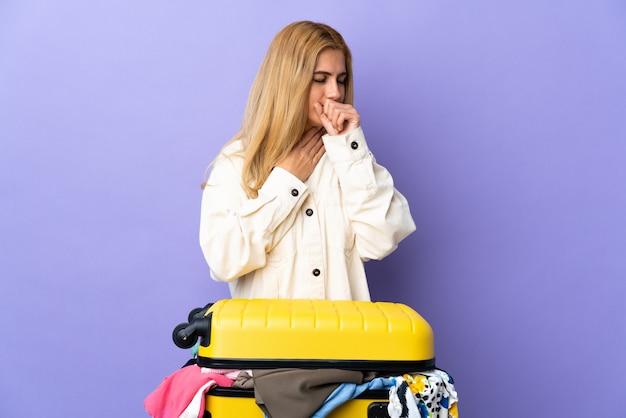 Молодая уругвайская белокурая женщина с чемоданом, полным одежды над фиолетовой стеной, много кашляет