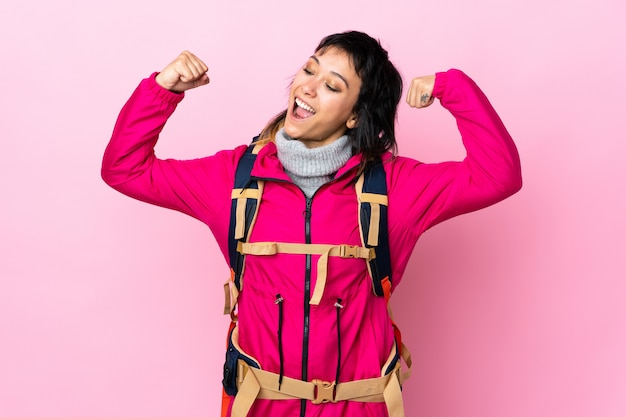 Молодая девушка альпиниста с большим рюкзаком над изолированной розовой стеной празднует победу