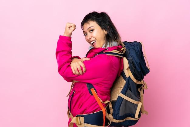 Молодая девушка-альпинистка с большим рюкзаком над изолированной розовой стеной делает сильный жест