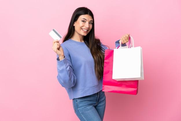 Молодая брюнетка девушка над розовой стеной, холдинг сумок и кредитная карта