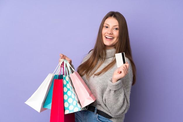 Девушка подростка кавказская изолированная на фиолетовой стене держа хозяйственные сумки и кредитную карточку