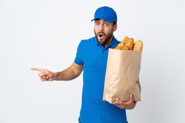 Доставка человек, держащий мешок, полный хлеба, изолированные на белом удивлен и указывая сторону