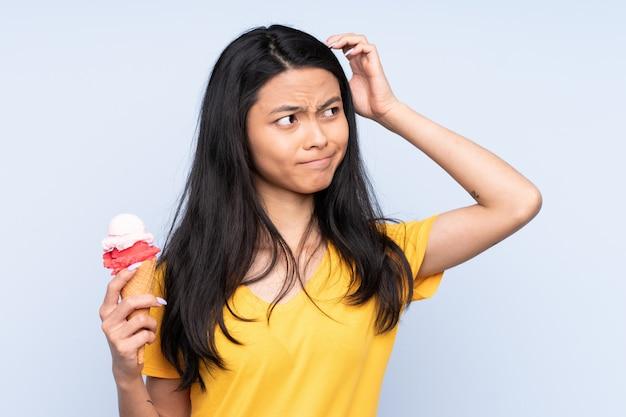 Азиатская девушка подростка с корнет мороженым, изолированных на синей стене, с сомнением и с смутным выражением лица