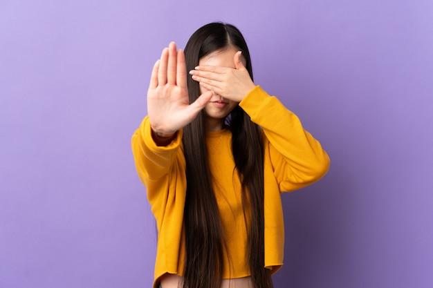 孤立した紫停止ジェスチャーを作ると顔を覆っている若い中国人の女の子