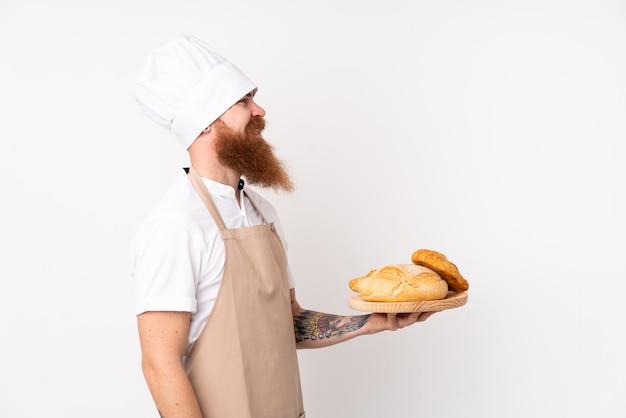 シェフの制服を着た赤毛の男。幸せな表情でいくつかのパンのテーブルを保持している男性のパン屋