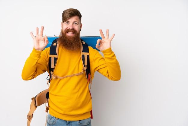 Молодой человек альпиниста с большой рюкзак на белом фоне, показывая знак ок с пальцами