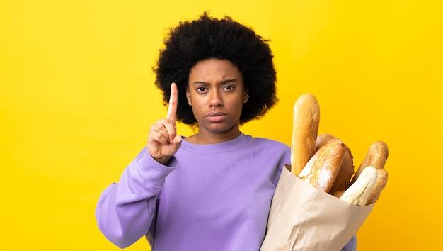 Молодая женщина, покупая хлеб на изолированном фоне