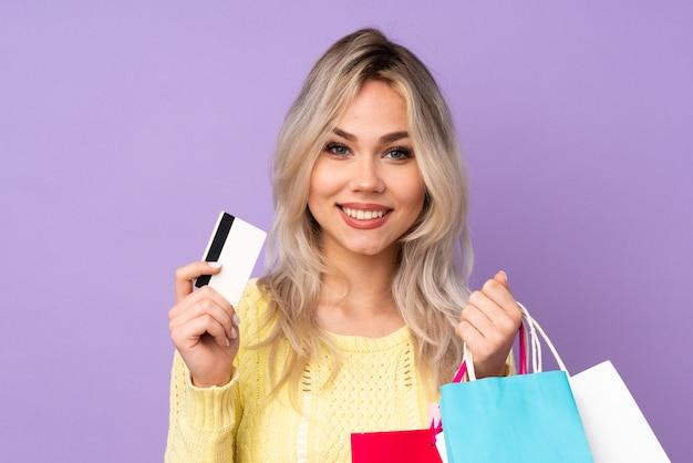 Молодая женщина, покупая одежду на изолированном фоне