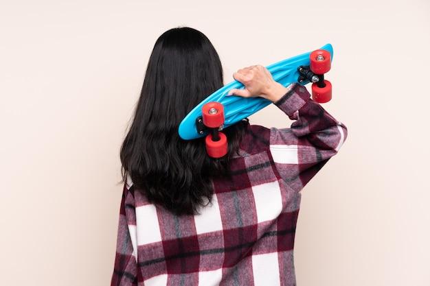 Молодая азиатская женщина делая конькобежец над изолированной предпосылкой