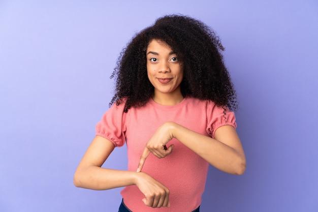 Молодая афро-американская женщина изолированная на пурпуре делая жест быть поздно