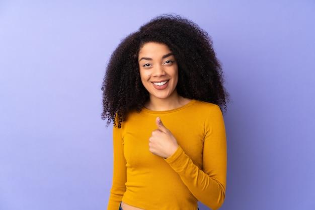 ジェスチャー親指を与える紫に分離された若いアフリカ系アメリカ人女性