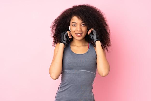 Молодая афро-американская женщина спорта изолированная на розовой слушая музыке