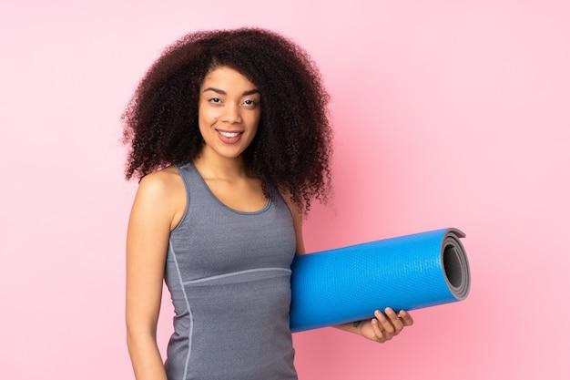 Молодая афро-американская женщина спорта изолированная на пинке с циновкой и усмехаться