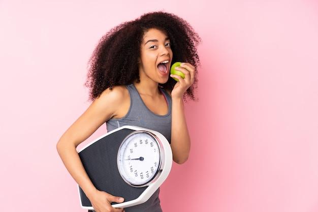 計量機とリンゴとピンクに分離された若いアフリカ系アメリカ人女性