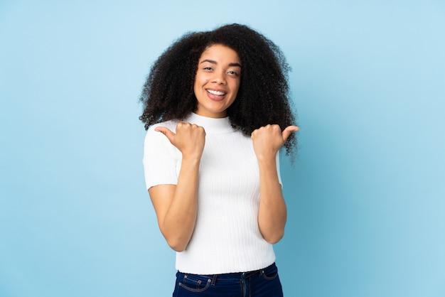 ジェスチャと笑顔の親指を持つ若いアフリカ系アメリカ人女性