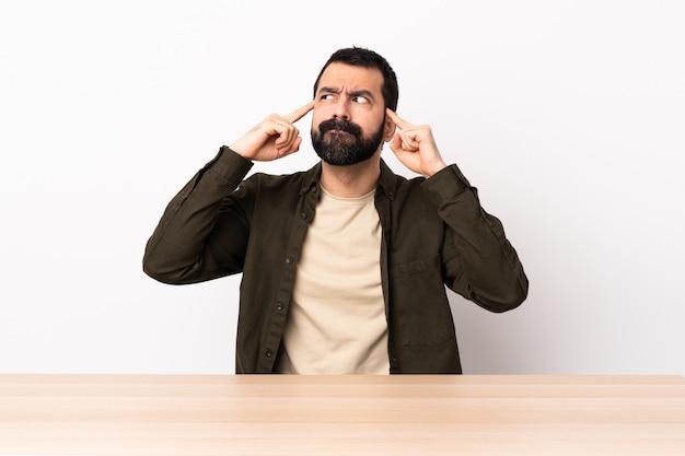 疑問と考えを持つテーブルでひげを持つ白人男。