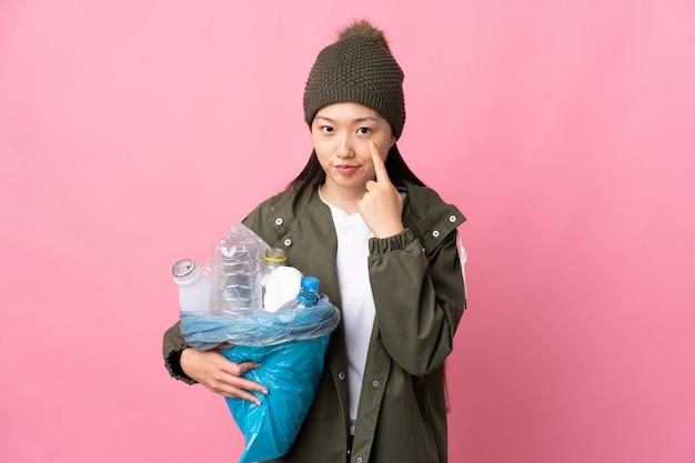 何かを示す孤立したピンクでリサイクルするペットボトルの完全な袋を保持している中国の女の子