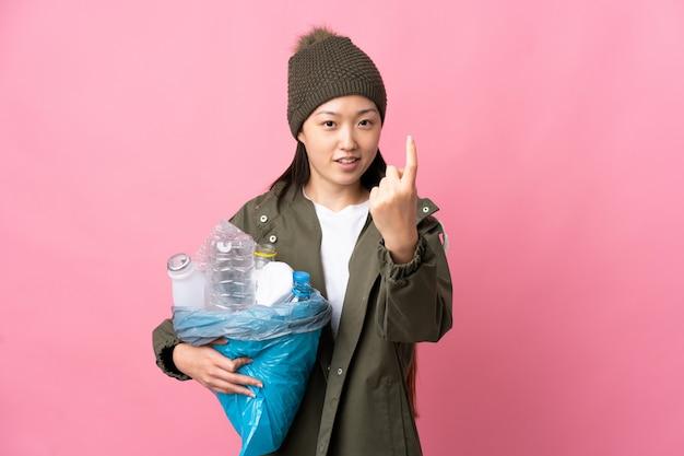 今後のジェスチャーを行う孤立したピンクでリサイクルするペットボトルの完全な袋を保持している中国の女の子
