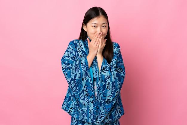 Молодая китайская девушка носить кимоно, счастливый и улыбающийся конус рот руками